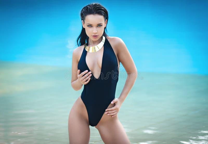 性感的比基尼泳装的美丽的妇女在海滩 免版税库存照片