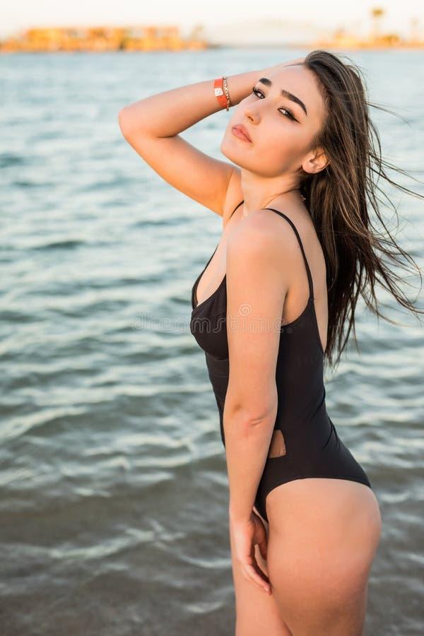 性感的比基尼泳装身体妇女嬉戏在获得天堂热带的海滩使用的乐趣飞溅水 旅行的VA美丽的适合身体女孩 库存图片