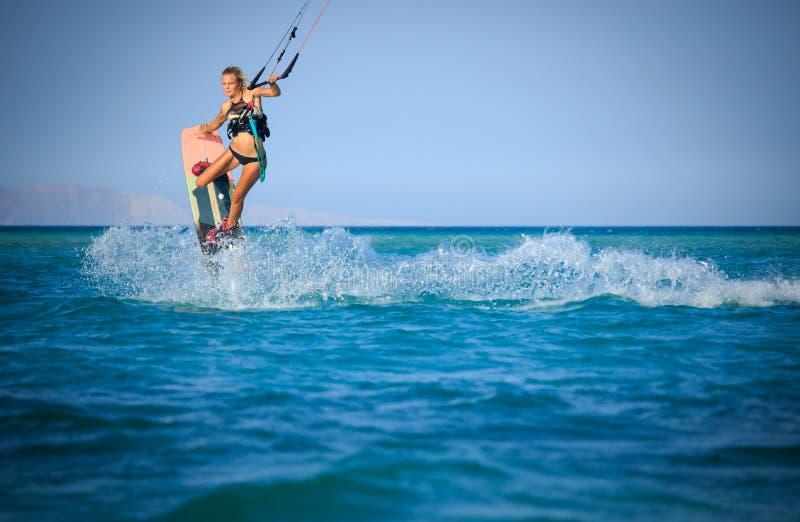 性感的泳装的风筝冲浪的女孩有在天空的风筝的在船上在蓝色与水飞溅的海乘坐的波浪 消遣活动 库存图片