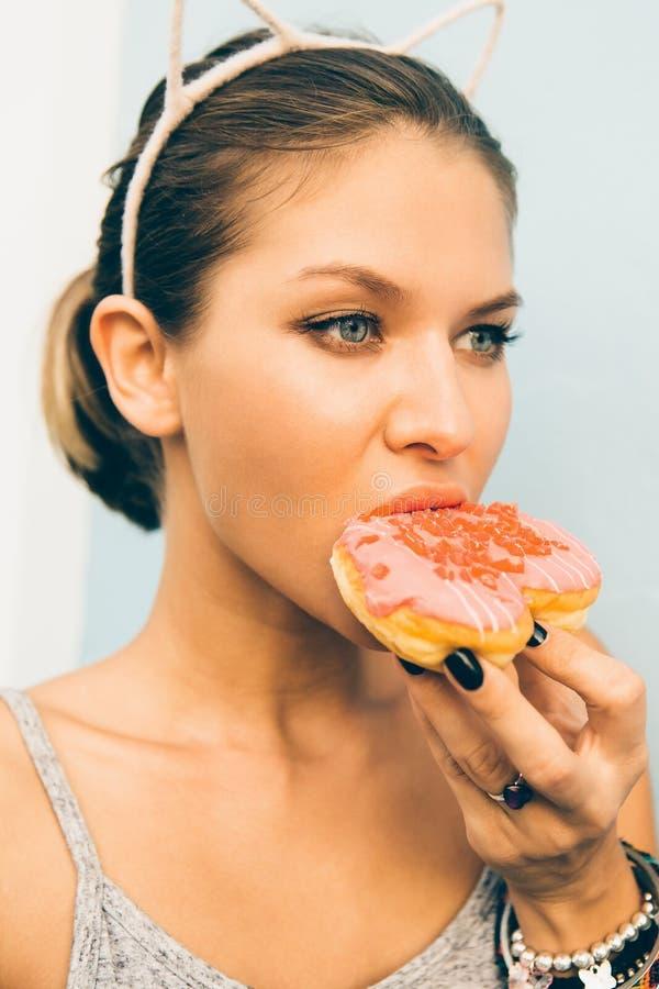 性感的深色的夫人吃甜心被塑造的多福饼 免版税图库摄影