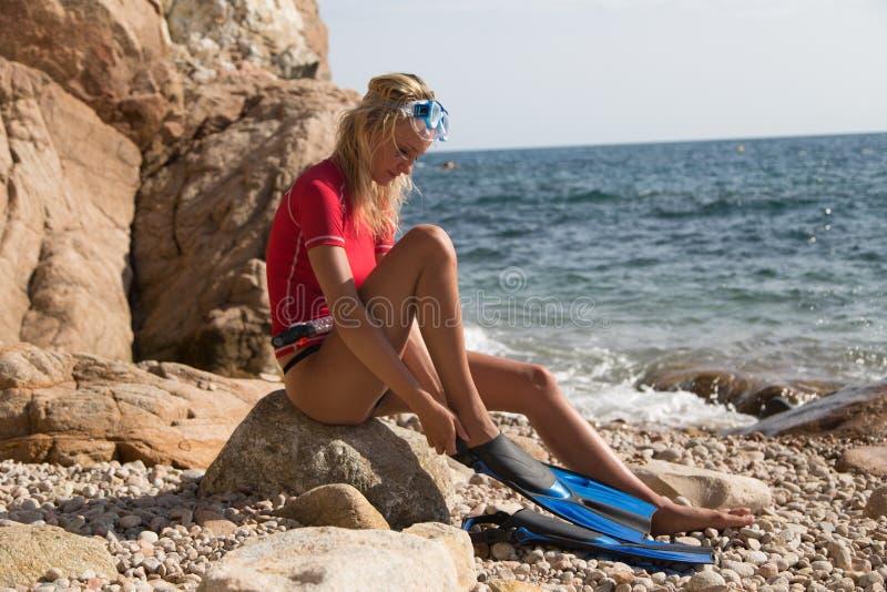 性感的潜水者女孩坐多岩石的海滩和预习功课的峭壁 免版税库存照片