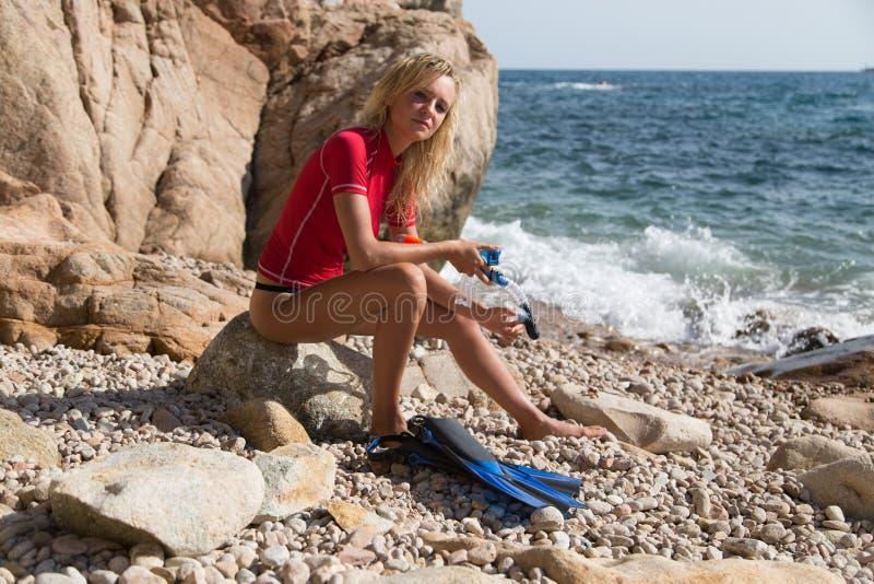 性感的潜水者女孩坐多岩石的海滩和预习功课的峭壁 图库摄影