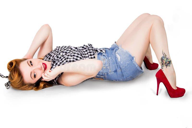性感的画报女孩简而言之说谎在与手机的一个地板上的和高跟鞋 免版税库存照片