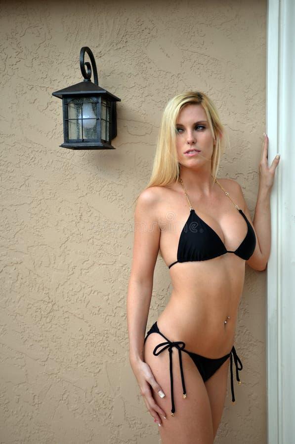性感的白肤金发的佩带的黑比基尼泳装 免版税库存照片