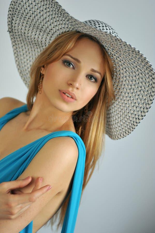 年轻性感的白肤金发的女孩佩带的夏天帽子画象  免版税库存图片