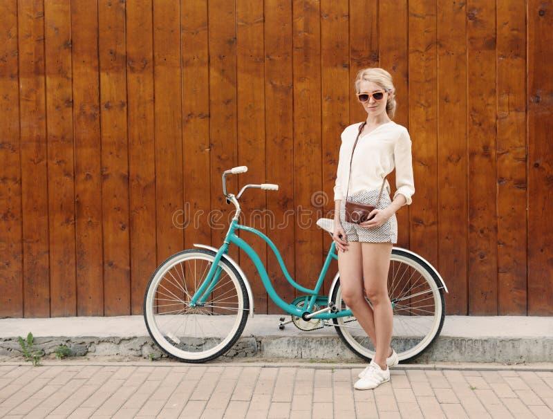 年轻性感的白肤金发的女孩在有棕色葡萄酒照相机的葡萄酒绿色自行车附近站立在橙色太阳镜 温暖, tonning 库存图片