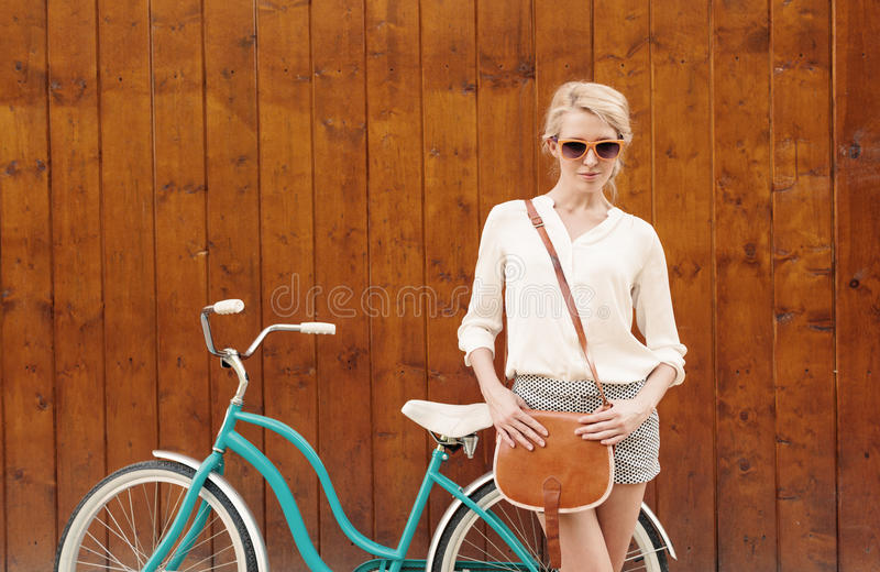 年轻性感的白肤金发的女孩在有棕色葡萄酒袋子的葡萄酒绿色自行车附近站立在橙色太阳镜,温暖, tonning 免版税库存照片