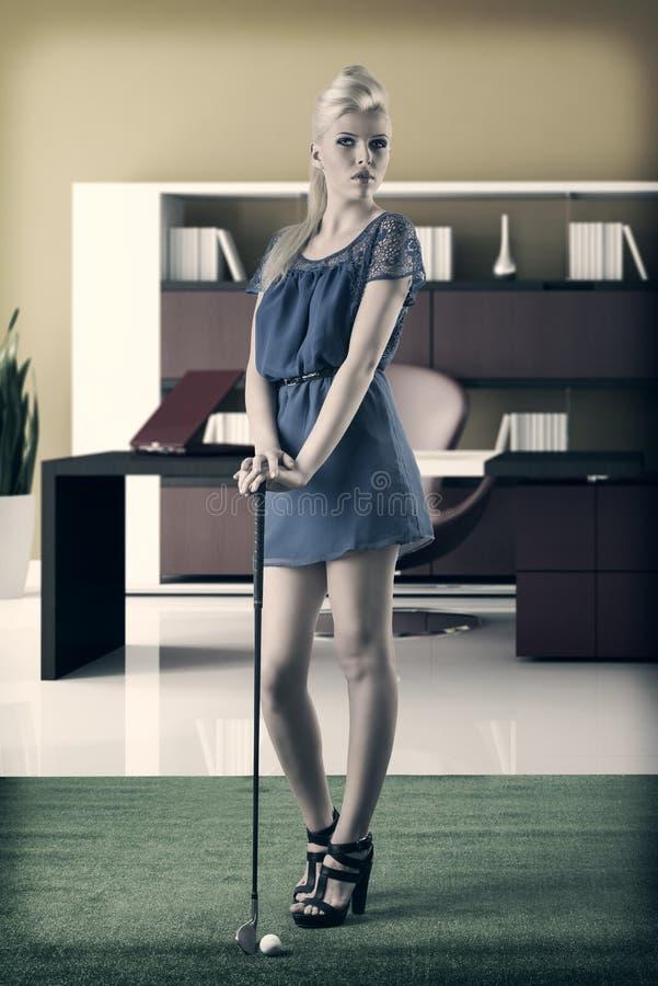 性感的白肤金发的女孩支付高尔夫球,在葡萄酒样式 库存图片