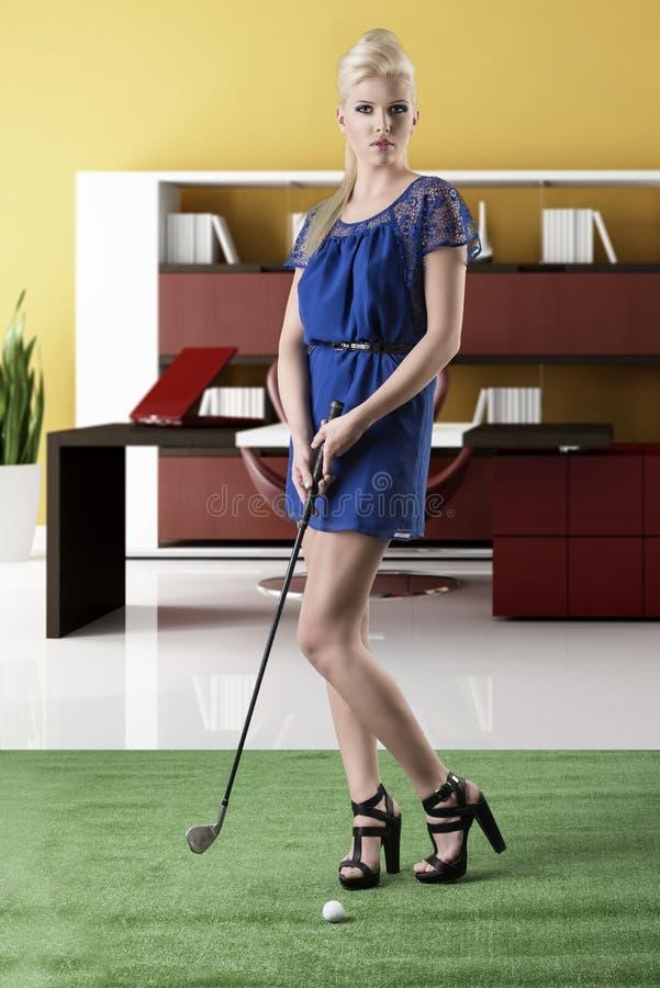 性感的白肤金发的女孩支付高尔夫球,浏览透镜 库存照片