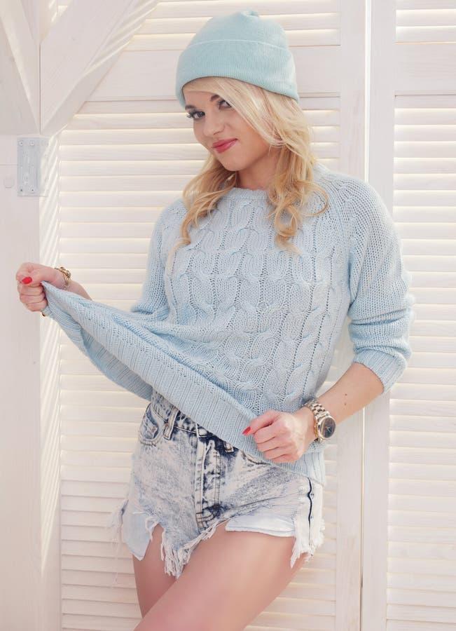 性感的白肤金发的妇女佩带的短裤毛线衣和帽子 库存照片