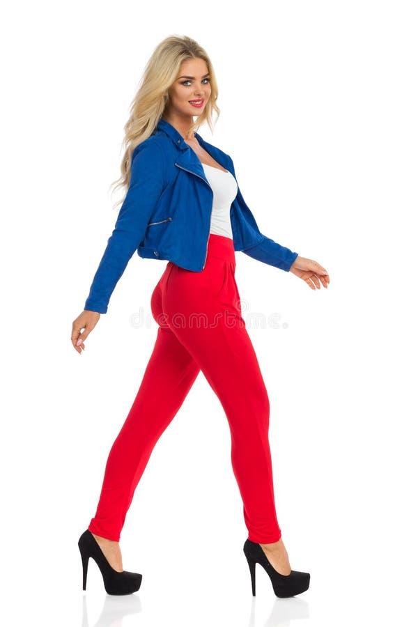性感的白肤金发的妇女在夹克、红色裤子和高跟鞋走 库存照片