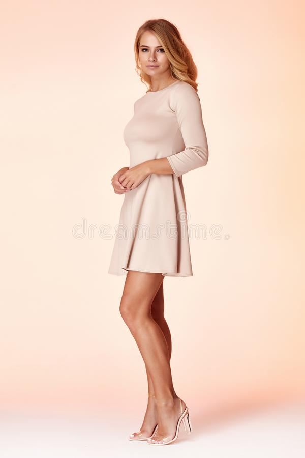 性感的白肤金发的妇女皮包骨头的企业样式礼服米黄颜色完善的身材饮食繁忙的魅力夫人便装样式秘书 库存图片