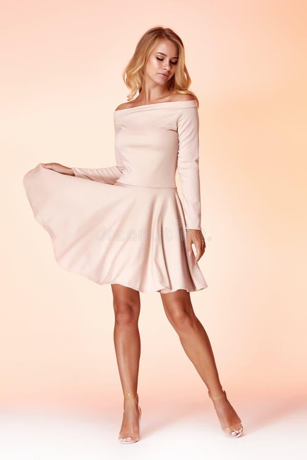 性感的白肤金发的妇女皮包骨头的企业样式礼服米黄颜色完善的身材饮食繁忙的魅力夫人便装样式秘书 免版税库存图片