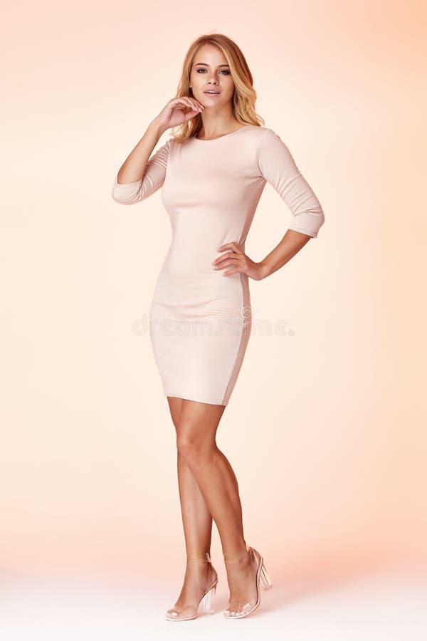 性感的白肤金发的妇女皮包骨头的企业样式礼服米黄颜色完善的身材饮食繁忙的魅力夫人便装样式秘书 免版税库存照片