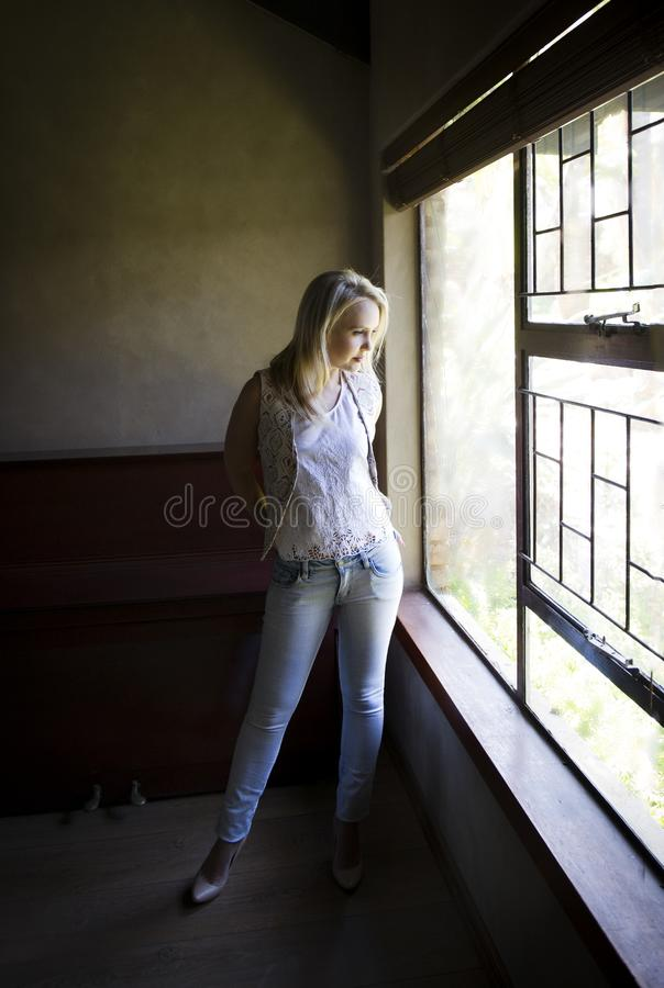 性感的白肤金发的摆在窗口旁边的妇女佩带的背心用她的在她的口袋的手 免版税库存照片