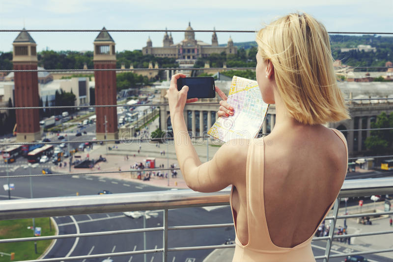 性感的礼服的美丽的女孩有的开背部是城市的被拍摄的全景 库存图片