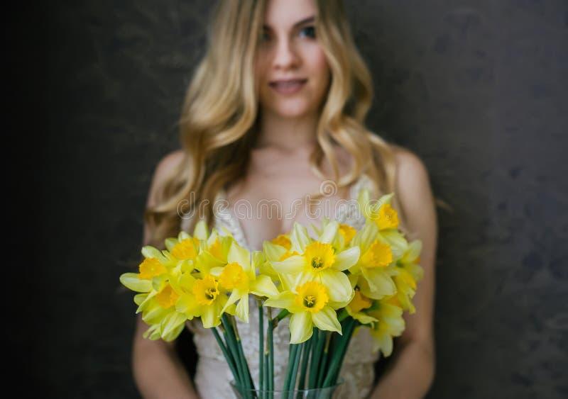 性感的米黄女用贴身内衣裤的美丽的性感的白肤金发的妇女有春天的开花黄水仙花束  在花的有选择性的fokus 库存图片