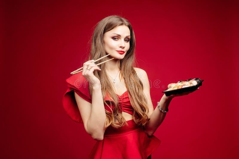 性感的红色礼服的妇女吃鲜美寿司的在演播室 库存照片