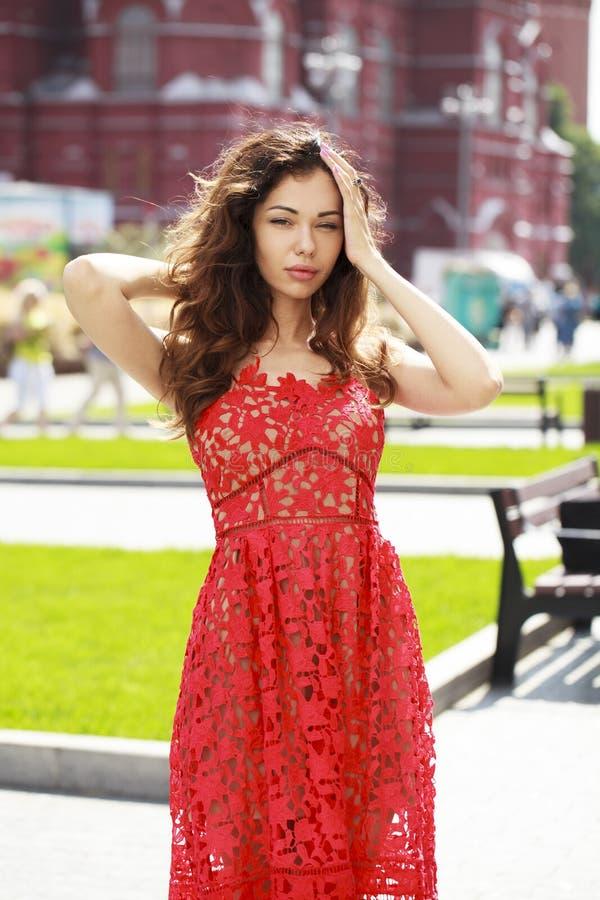 性感的红色礼服的美丽的深色的妇女 库存照片