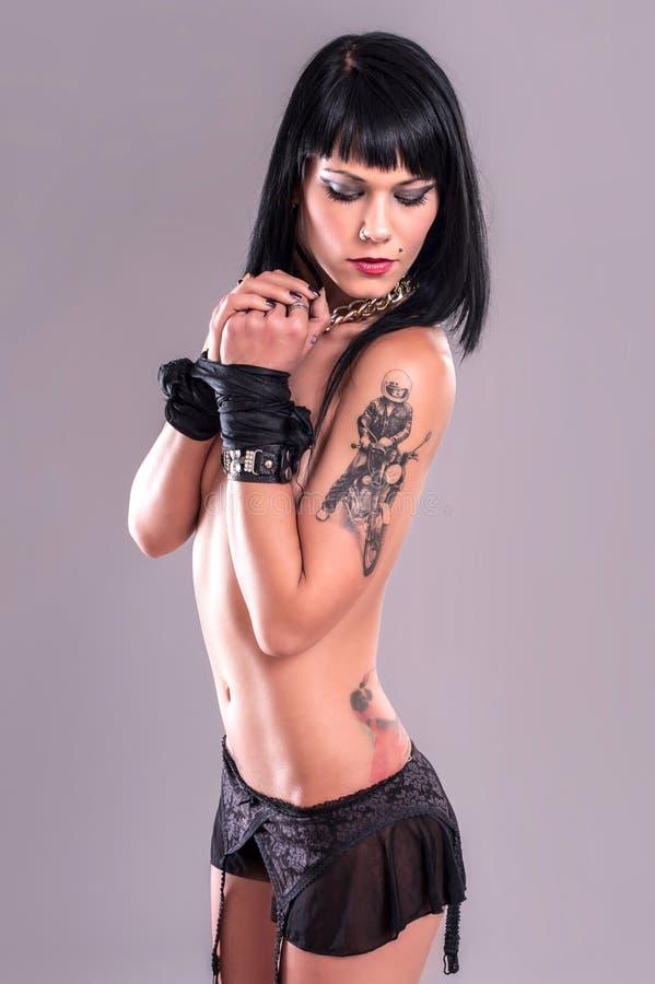 性感的纹身花刺女孩用被绑住的手 免版税库存图片
