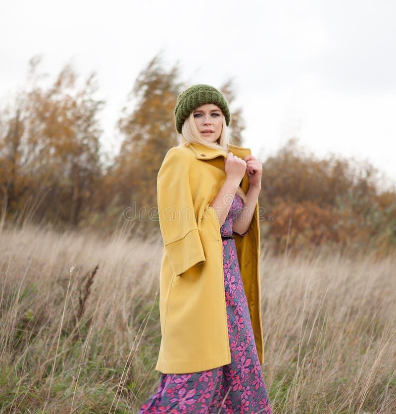 性感的美丽的妇女画象被编织的绿色帽子和黄色外套的, smokey注视构成,飞行在干草的头发 免版税图库摄影