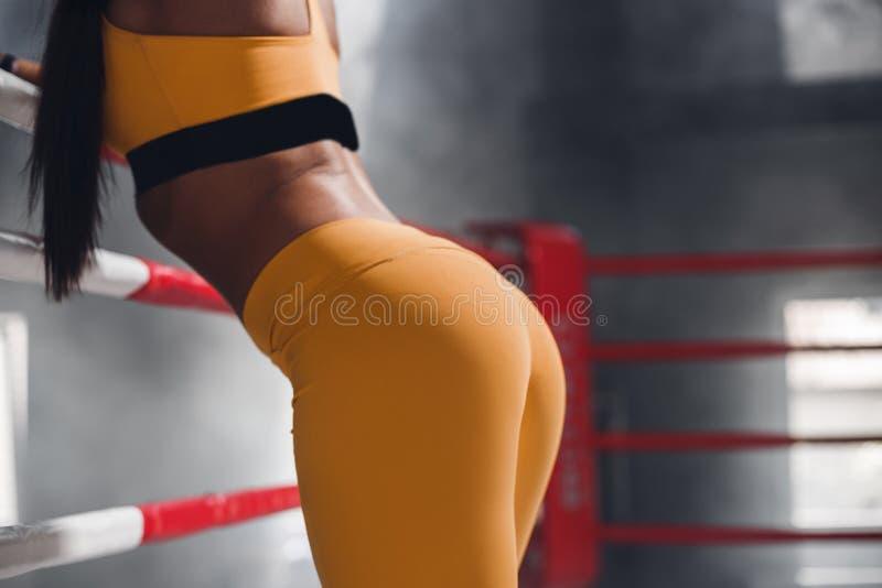 性感的美丽的运动驴子,女性在倾斜在绳索的拳击台 免版税库存照片