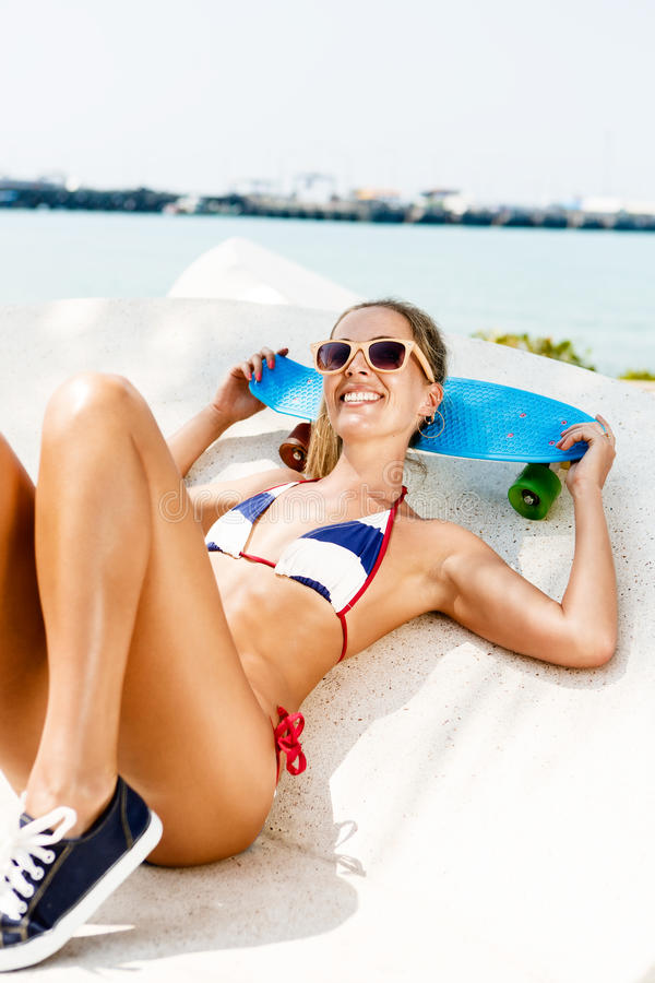 性感的被晒黑的夫人与蓝色便士板坐海滩 免版税库存图片