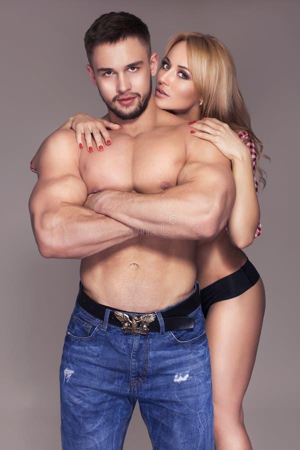 性感的适合干涉了在牛仔裤和裤子和格子花呢披肩T恤杉的夫妇  免版税库存照片