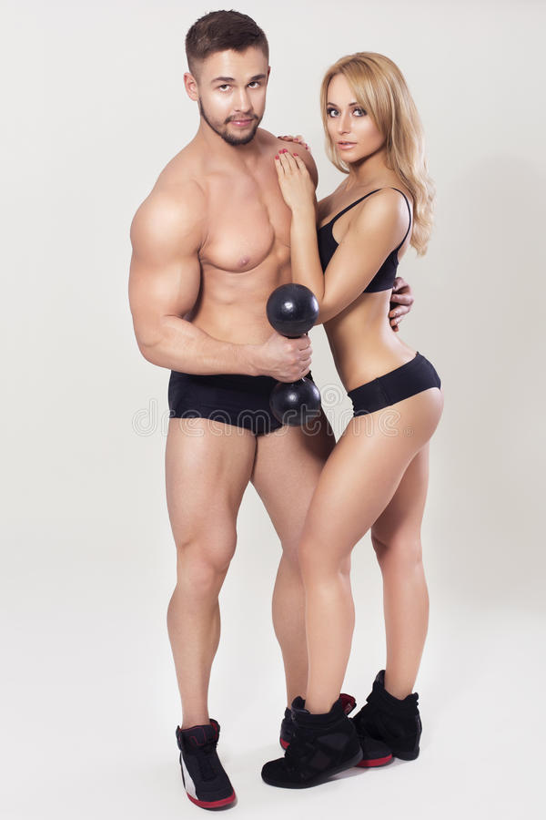 性感的适合干涉了在运动服的夫妇在中立灰色背景 免版税库存照片
