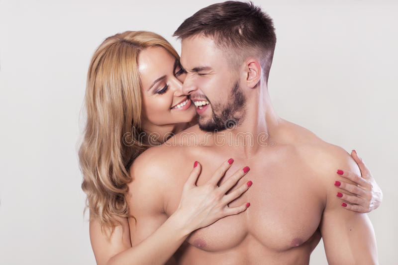 性感的适合干涉了在运动服的夫妇在中立灰色背景 免版税图库摄影