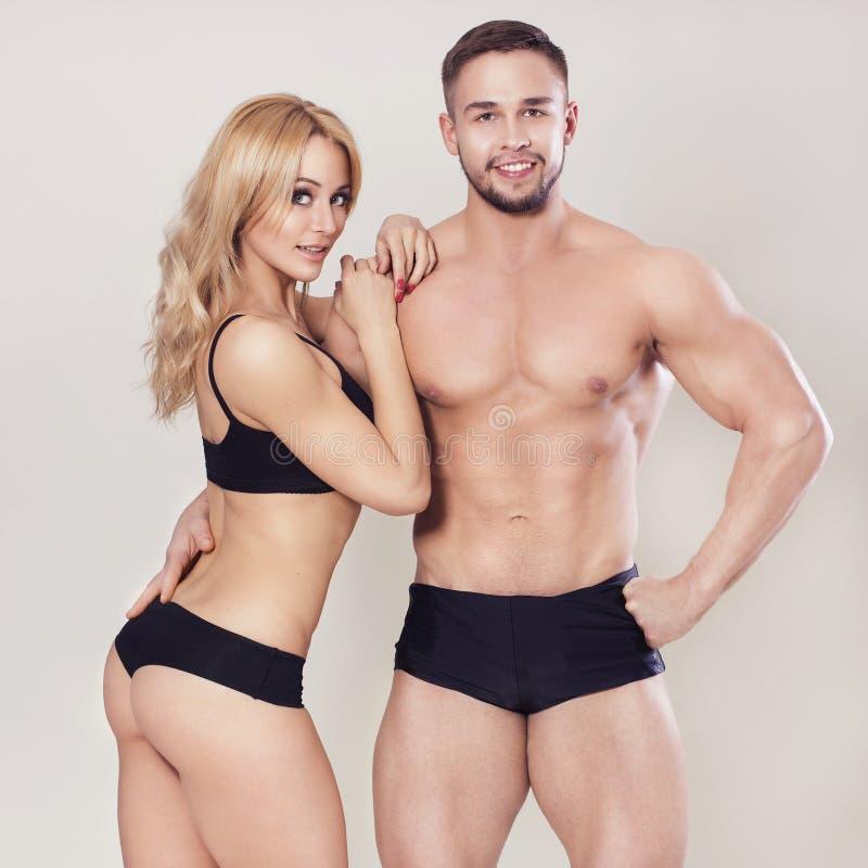 性感的适合干涉了在运动服的夫妇在中立灰色背景 库存图片