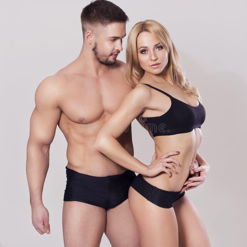 性感的适合干涉了在运动服的夫妇在中立灰色背景 免版税库存图片