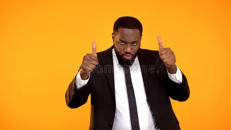 性感的非洲商人陈列翘拇指,庆祝成功的起动,胜利 免版税库存图片