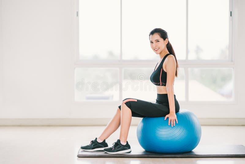 性感的年轻亚洲女孩锻炼,在健身球的微笑在干净的家庭健身房,体育俱乐部 瑜伽有氧类,体育教练员 库存照片