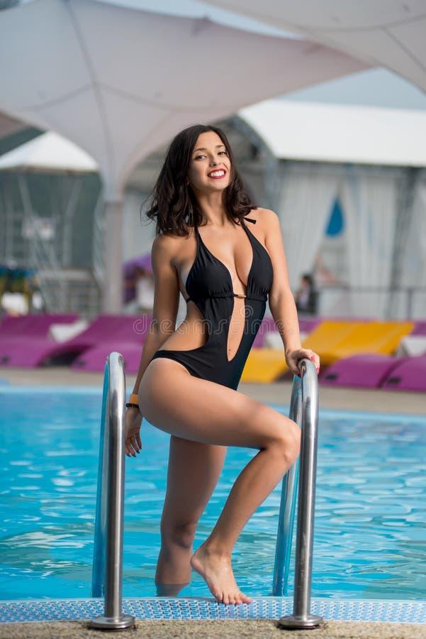 性感的黑比基尼泳装的年轻微笑的妇女有匀称身体的在手段的游泳池附近摆在 库存图片