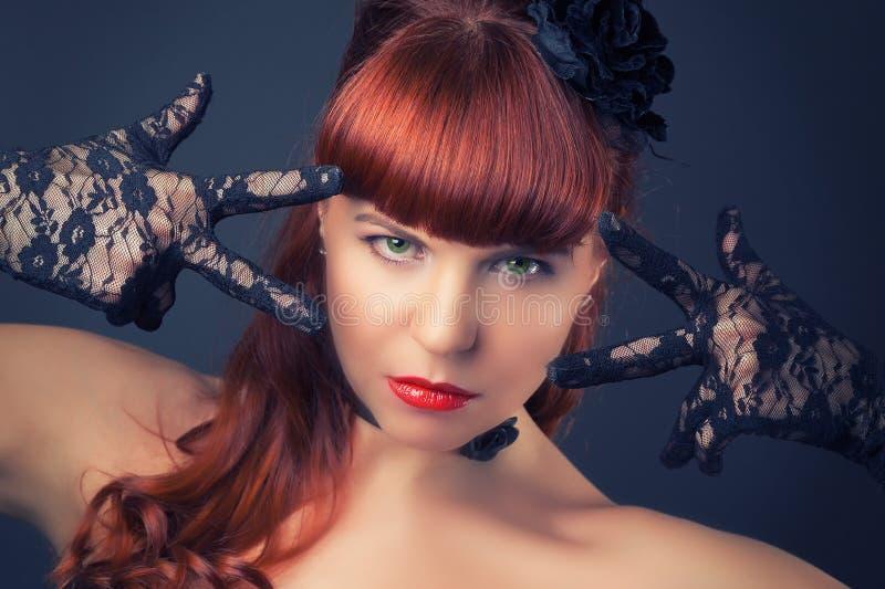 性感的黑缎束腰的哥特式红头发人妇女反对黑暗的gre 免版税库存图片