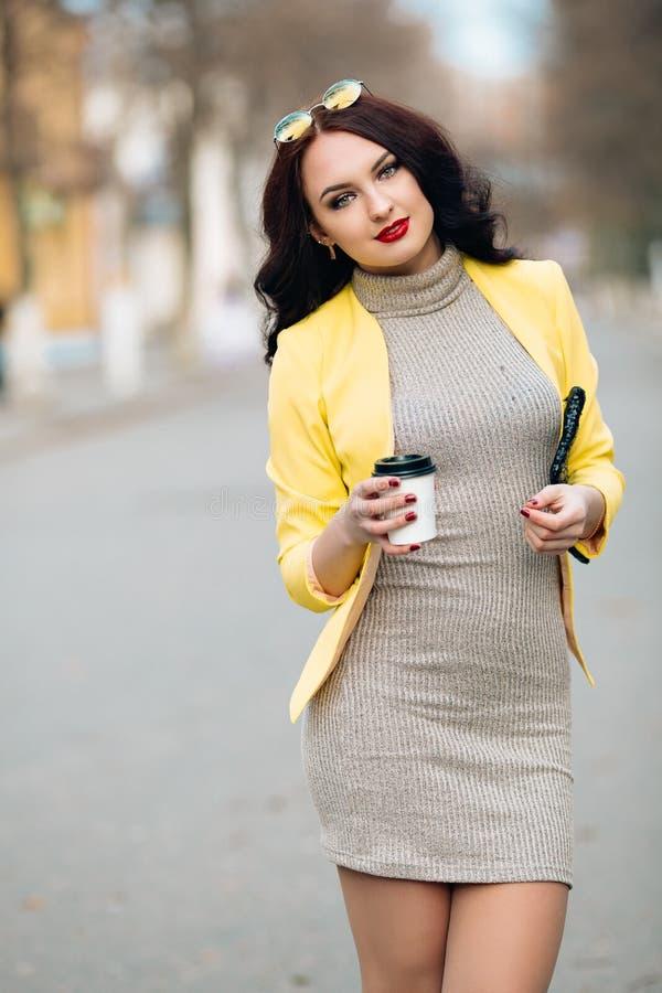 性感的年轻美丽的妇女特写镜头滑稽的画象有明亮的构成和红色嘴唇的,一份温暖的饮料可口咖啡 免版税库存图片