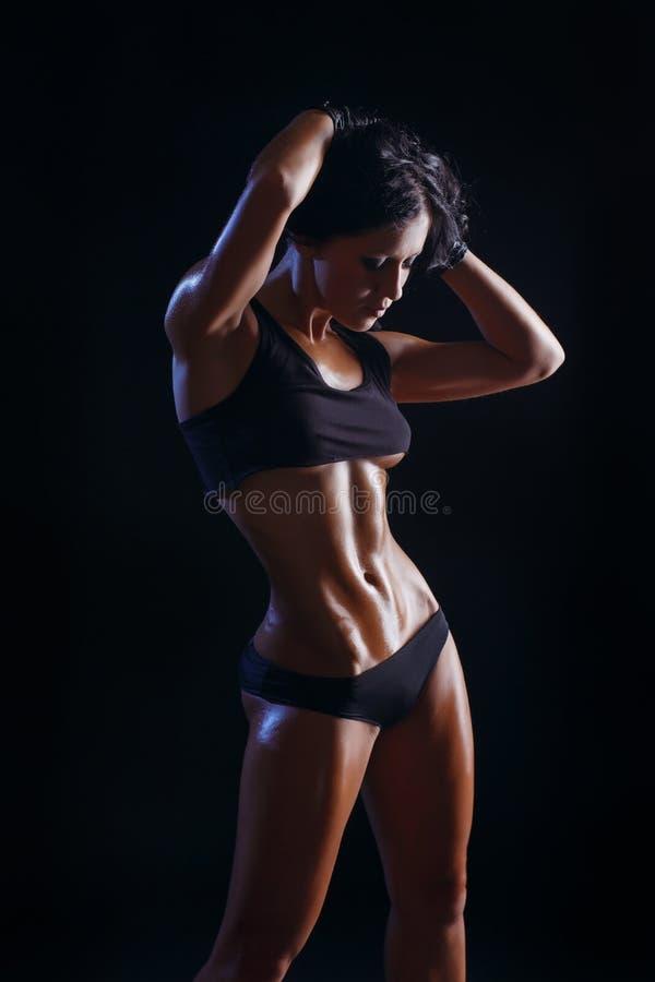 性感的年轻肌肉的摆在黑背景的健身深色的女孩 免版税库存图片