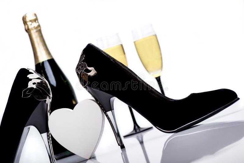 性感的黑高跟鞋、心脏、香宾和玻璃 免版税图库摄影