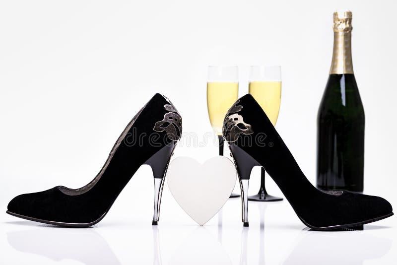 性感的黑高跟鞋、心脏、香宾和玻璃 库存图片