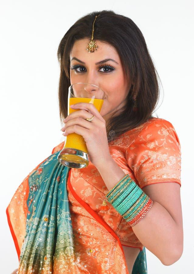 性感饮用的女孩汁液的芒果 免版税库存图片