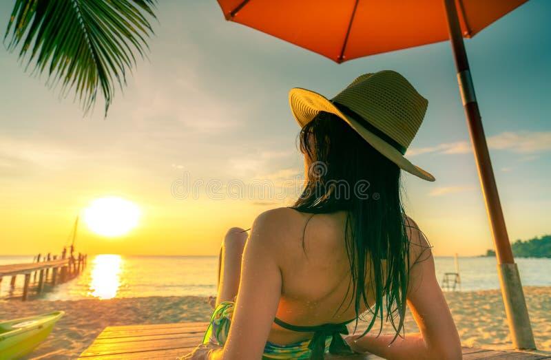 性感,享用并且放松说谎和晒日光浴在sunbed的白种人女服比基尼泳装在沙滩在天堂热带海岛下 免版税库存图片