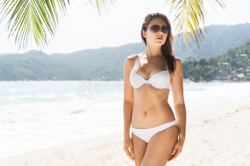 性感,少妇佩带的太阳镜和引诱的白色泳装 免版税库存图片