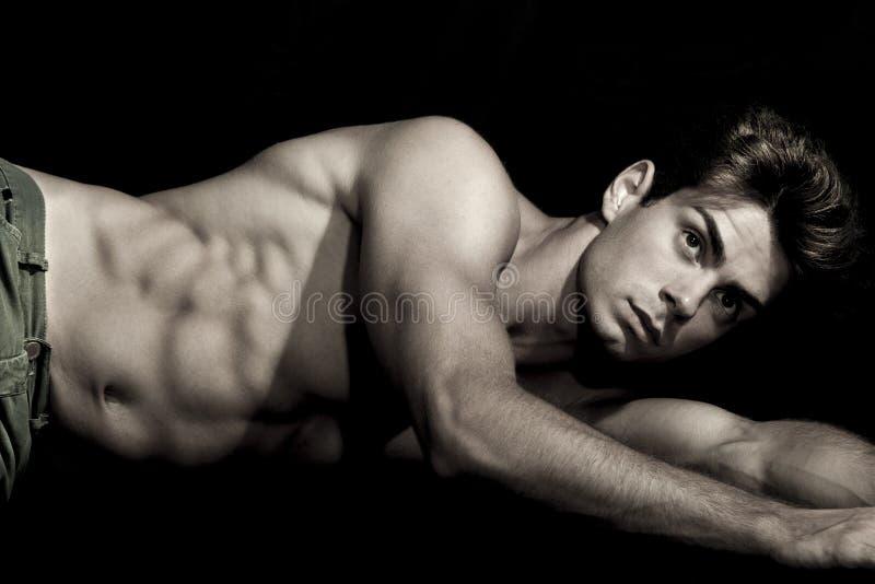 性感年轻人赤裸上身说谎在地面上 健身房强健的身体 免版税图库摄影