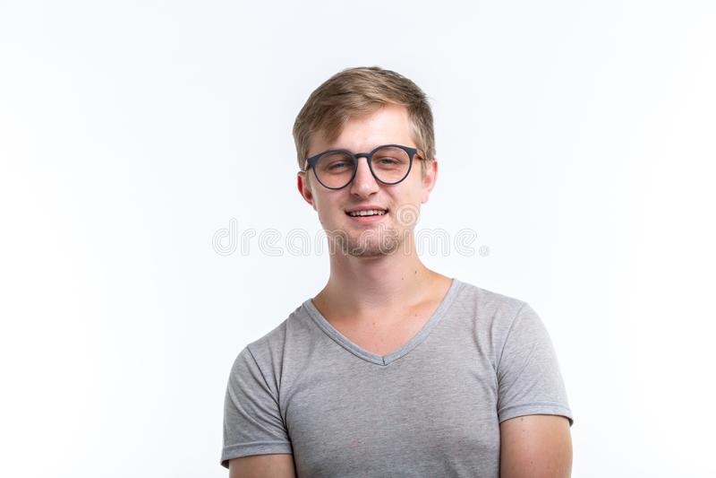 怪杰,教育,人概念-在白色背景的年轻人看,如他是书呆子 库存图片