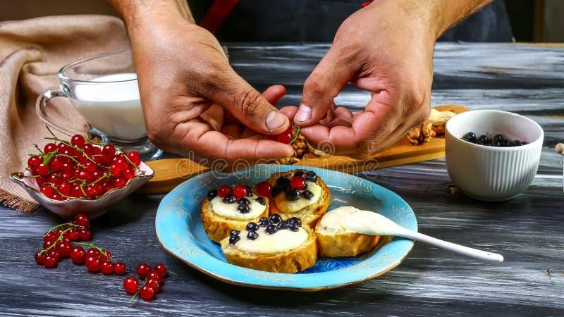 总体上烹调bruschetta用蓝莓和红浆果,奶油奶酪,蜂蜜五谷烤面包-在深黑色 免版税库存图片