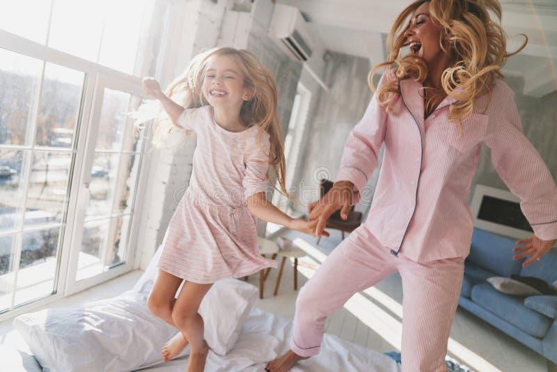 总是愉快一起 跳跃在床上的逗人喜爱的小女孩与 免版税库存照片