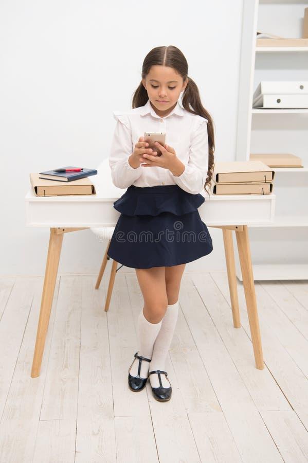 总是有联系 孩子女孩传送信息到父母 女小学生微笑的面孔短信的朋友 女孩通知的父母标记 免版税库存图片