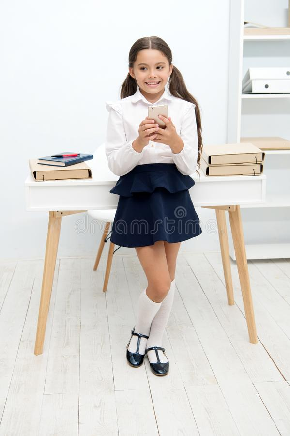 总是有联系 孩子女孩传送信息到父母 女小学生笨拙微笑的面孔有坏消息 女孩紧张通知 图库摄影