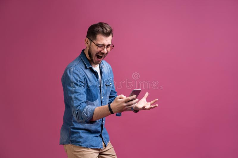 总是有联系 微笑的年轻人藏品智能手机和看它 一个愉快的人的画象使用手机的 免版税库存照片